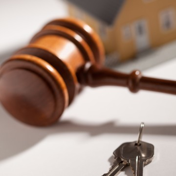Gavel, House Keys and Model Home on Gradated Background with Selective Focus.