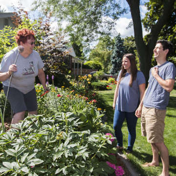 Photo of Niagara resident and students laughing in a garden